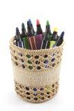 Marcadores coloreados en cesta en el fondo blanco Imagenes de archivo