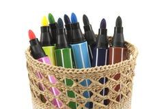 Marcadores coloreados en cesta en el fondo blanco Foto de archivo