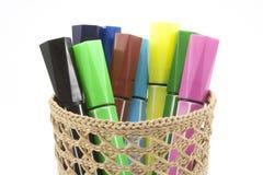 Marcadores coloreados en cesta en el fondo blanco Fotografía de archivo libre de regalías