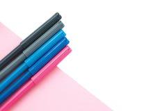 Marcadores coloreados en el fondo blanco y rosado Imagen de archivo