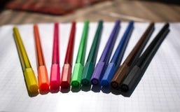 Marcadores coloreados en la hoja del cuaderno foto de archivo