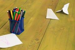 Marcadores coloreados en una caja azul del metal Hojas del papel Imagen de archivo