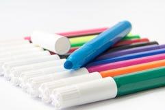 Marcadores coloreados y uno abiertos en un fondo blanco foto de archivo libre de regalías