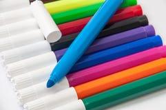 Marcadores coloreados y uno abiertos en un fondo blanco Fotos de archivo