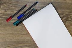Marcadores pretos, vermelhos, verdes e azuis e uma folha de papel branca na tabela imagens de stock