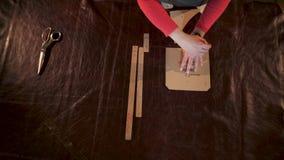 Marcas de mestre a pele animal tratada Aplica e segue um molde do cartão em uma oficina pequena do ofício filme