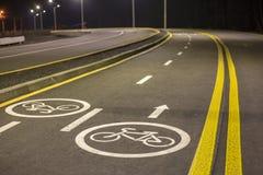 Marcas y muestras de camino de la bicicleta Carril iluminado del viaje del carril de bicicleta reservado para los ciclistas con l imagen de archivo libre de regalías