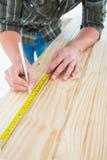 Marcatura del carpentiere con la misura di nastro sulla plancia di legno Fotografie Stock Libere da Diritti