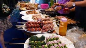 Marché asiatique traditionnel de nourriture de rue de nuit en Thaïlande Boulettes de viande de barbecue et d'autres casse-croûte  banque de vidéos