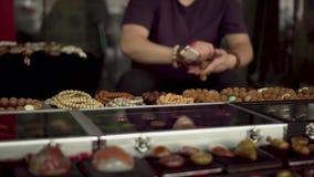 Marché aux puces asiatique un homme faisant le bracelet de chinois traditionnel banque de vidéos