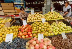 Marché avec des pommes, des raisins et des vendeurs féminins occupés attendant des clients des fruits frais Photographie stock