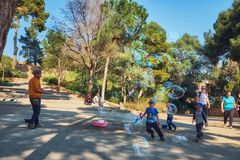 March 2017, Barcelona, Spain - Man blowing giant bubbles in the Guel park. Street performer inflating huge bubbles for stock image