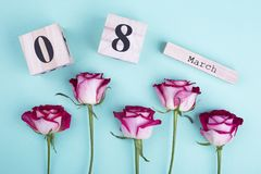 March 8 calendar and roses. Large wooden calendar and roses. Beautiful flowers on natural background stock image