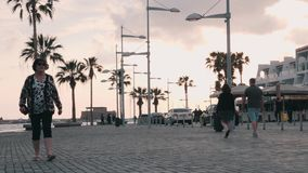 March, 16, 2019/Cyprus, Paphos Beautiful quay with cars and pedestrian path. Tourists walking on promenade in Paphos, Cyprus. Tour. Ist promenade with palms stock footage