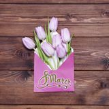 8 March. Happy women's day! Card with Pink tulips in envelope. 8 March. Happy women's day! Card with Pink tulip flowers in envelope on brown wooden Royalty Free Stock Photography