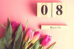 8 March Happy Women`s Day concept. With wooden block calendar and pink tulips on pink background. Copy space. 8 March Happy Women`s Day concept. With wooden Royalty Free Stock Photography