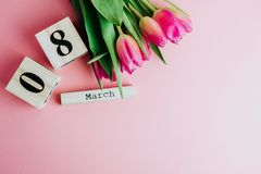 8 March Happy Women`s Day concept. With wooden block calendar and pink tulips on pink background. Copy space. 8 March Happy Women`s Day concept. With wooden Stock Photos