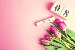 8 March Happy Women`s Day concept. With wooden block calendar and pink tulips on pink background. Copy space. 8 March Happy Women`s Day concept. With wooden Royalty Free Stock Images