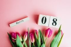8 March Happy Women`s Day concept. With wooden block calendar and pink tulips on pink background. Copy space. 8 March Happy Women`s Day concept. With wooden Royalty Free Stock Photos