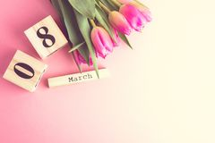 8 March Happy Women`s Day concept. With wooden block calendar and pink tulips on pink background. Copy space. 8 March Happy Women`s Day concept. With wooden Royalty Free Stock Image