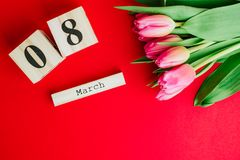 8 March Happy Women`s Day concept. With wooden block calendar and pink tulips on red background. Copy space. 8 March Happy Women`s Day concept. With wooden block Stock Photo