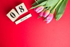 8 March Happy Women`s Day concept. With wooden block calendar and pink tulips on red background. Copy space. 8 March Happy Women`s Day concept. With wooden block Royalty Free Stock Photos