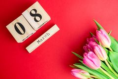 8 March Happy Women`s Day concept. With wooden block calendar and pink tulips on red background. Copy space. 8 March Happy Women`s Day concept. With wooden block Stock Photos