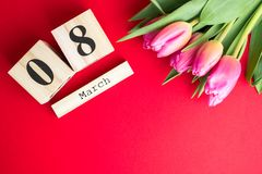 8 March Happy Women`s Day concept. With wooden block calendar and pink tulips on red background. Copy space. 8 March Happy Women`s Day concept. With wooden block Royalty Free Stock Images