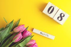 8 March Happy Women`s Day concept. With wooden block calendar and pink tulips on yellow background. Copy space. 8 March Happy Women`s Day concept. With wooden Stock Photography