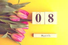 8 March Happy Women`s Day concept. With wooden block calendar and pink tulips on yellow background. Copy space. 8 March Happy Women`s Day concept. With wooden Stock Images