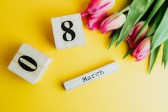8 March Happy Women`s Day concept. With wooden block calendar and pink tulips on yellow background. Copy space. 8 March Happy Women`s Day concept. With wooden Royalty Free Stock Photo
