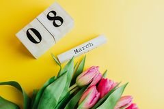 8 March Happy Women`s Day concept. With wooden block calendar and pink tulips on yellow background. Copy space. 8 March Happy Women`s Day concept. With wooden Royalty Free Stock Photography