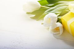 8 march happy womens day. White tulips and gift box on a white table
