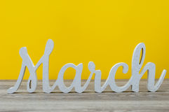 March - inscription carved out of wood on table with sunny yellow background. Spring beginning concept Royalty Free Stock Photo
