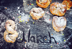 March 8, International Women`s Day, homemade buns. Sprinkled with powdered sugar and colored sprinkles on a black surface Stock Image