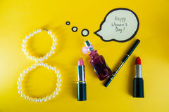 March 8, International Women`s Day. Set of women`s cosmetics and pearl necklace on golden backgroung. March 8, International Women`s Day. Set of women`s Stock Photo
