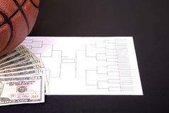 March Madness Bracket Basketball and Fanned Money on Black. A March Madness tournament bracket with a basketball and fanned money royalty free stock image