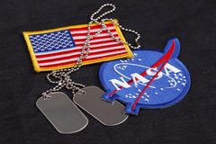 15 March 2018 - The National Aeronautics and Space Administration (NASA) emblem patch and dog tags on black uniform. Background stock photo