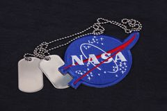 15 March 2018 - The National Aeronautics and Space Administration (NASA) emblem patch and dog tags on black uniform. Background royalty free stock photography