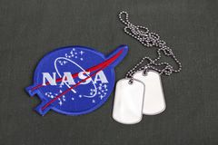 15 March 2018 - The National Aeronautics and Space Administration (NASA) emblem patch and dog tags on green uniform. Background royalty free stock photos