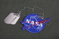 15 March 2018 - The National Aeronautics and Space Administration (NASA) emblem patch and dog tags on green uniform. Background stock photo