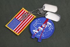 15 March 2018 - The National Aeronautics and Space Administration (NASA) emblem patch and dog tags on green uniform. Background stock image