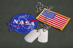 15 March 2018 - The National Aeronautics and Space Administration (NASA) emblem patch and dog tags on green uniform. Background royalty free stock photography