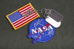 15 March 2018 - The National Aeronautics and Space Administration (NASA) emblem patch and dog tags on green uniform. Background stock photography