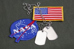 15 March 2018 - The National Aeronautics and Space Administration (NASA) emblem patch and dog tags on green uniform. Background stock photos