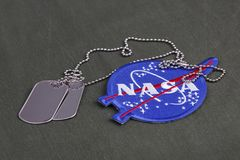 15 March 2018 - The National Aeronautics and Space Administration (NASA) emblem patch and dog tags on green uniform. Background royalty free stock images