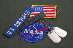 15 March 2018 - The National Aeronautics and Space Administration (NASA) emblem patch, dog tags, US AIR FORCE branch tape and US. Flag patch on green uniform royalty free stock photos