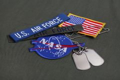15 March 2018 - The National Aeronautics and Space Administration (NASA) emblem patch, dog tags, US AIR FORCE branch tape and US. Flag patch on green uniform stock photography