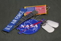 15 March 2018 - The National Aeronautics and Space Administration (NASA) emblem patch, dog tags, US AIR FORCE branch tape and US. Flag patch on green uniform royalty free stock photo