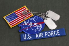 15 March 2018 - The National Aeronautics and Space Administration (NASA) emblem patch, dog tags, US AIR FORCE branch tape and US. Flag patch on green uniform royalty free stock images